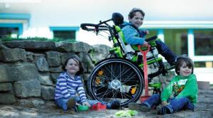 three children playing in a sandbox, two children sitting on the ground, one in a wheelchair