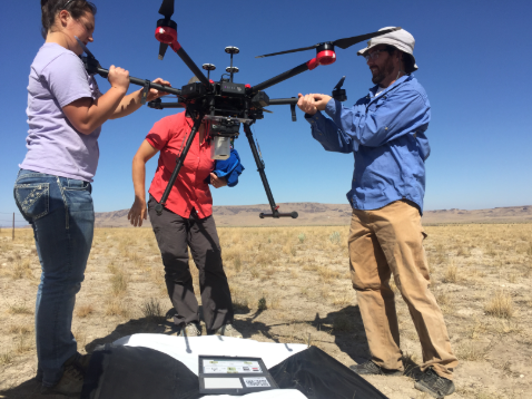 Team members handling and setting up large drone