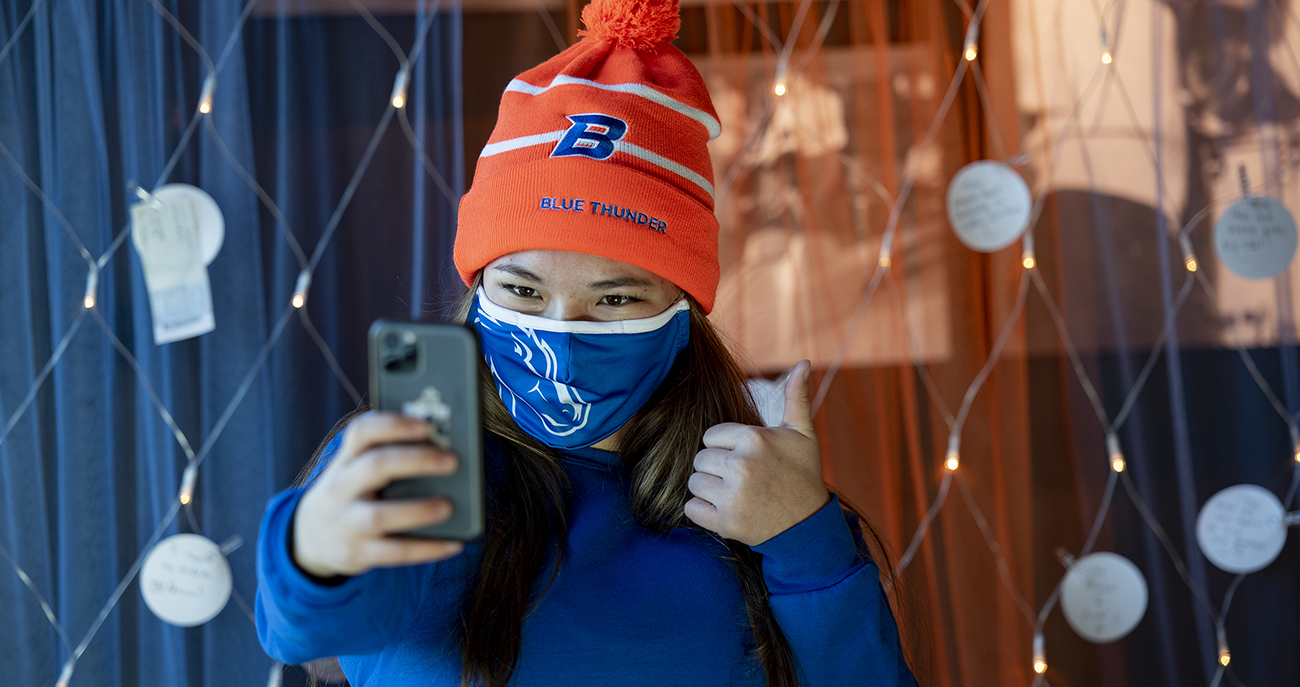 Student wearing a mask takes selfie in front of note wall